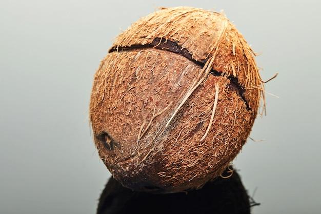 Świeży kokos z pęknięciem pośrodku na szaro