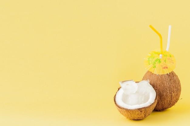 Świeży kokosowy koktajl z słoma na żółtym tle, kopii przestrzeń