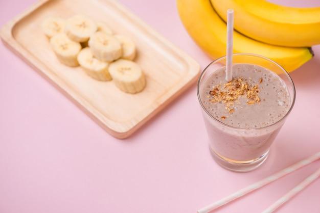 Świeży koktajl bananowy w szklance na różowym tle