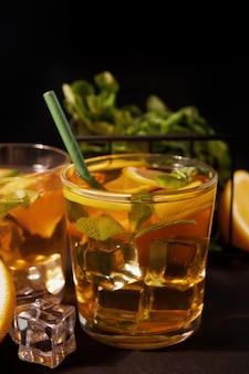 Świeży koktajl cuba libre z brązowym rumem, colą, miętą i limonką na czarnej powierzchni. koktajl long island iced tea.