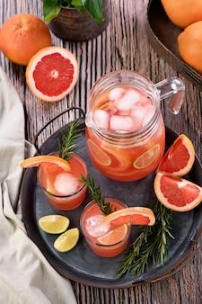 Świeży koktajl grejpfrutowy. świeży letni koktajl z grejpfrutem, limonką, gałązką rozmarynu i kostkami lodu.