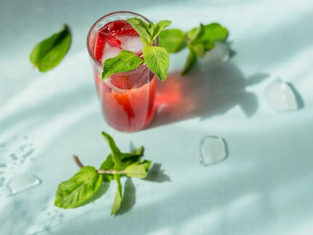 Świeży koktajl truskawkowy. letni różowy koktajl z truskawkami i kostkami lodu na jasnoniebieskim tle