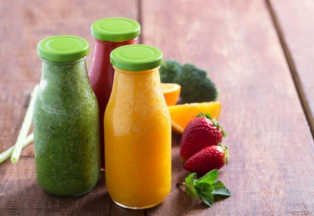 Świeży koktajl truskawkowy, pomarańczowy i brokuły w butelkach z owocami i warzywami na brązowym drewnianym stole rustykalnym