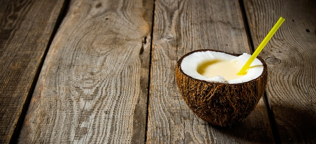 Świeży koktajl w kokosowej filiżance na drewnianym stole. wolne miejsce na tekst.
