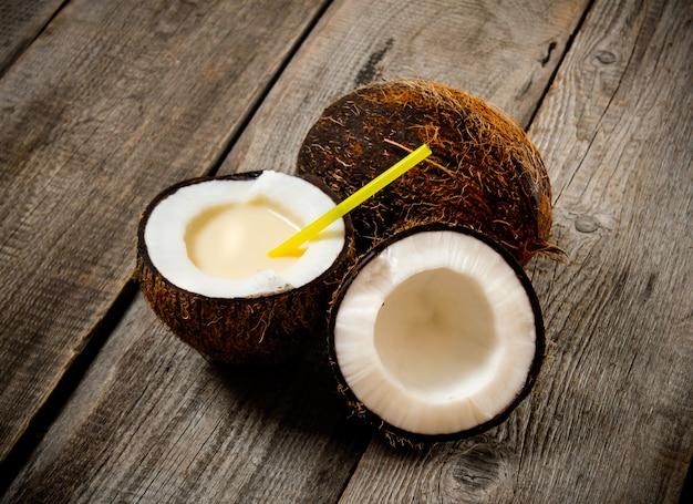 Świeży koktajl w kokosowej filiżance na drewnianym stole.