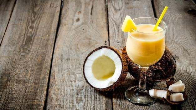 Świeży koktajl w szklance z kokosem na drewnianym stole. wolne miejsce na tekst.