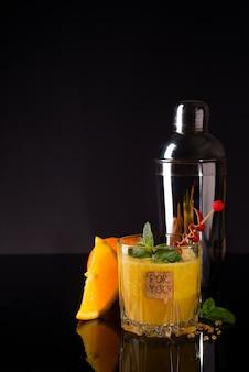 Świeży koktajl z pomarańczą, miętą i lodem na czarnym szklanym backgorund