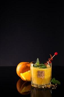 Świeży koktajl z pomarańcze, mennicą i lodem na czarnym szklanym backgorund, kopii przestrzeń
