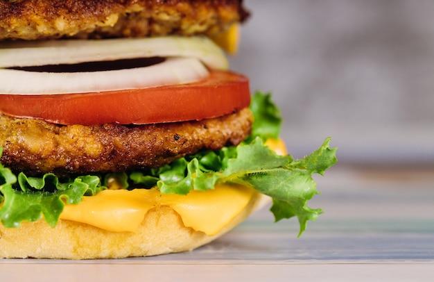 Świeży kolorowy domowej roboty hamburger na drewnianym stole.