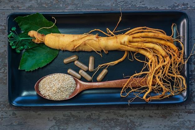 Świeży korzeń żeń-szenia na czarnej płycie z proszkiem do leków w kapsułkach