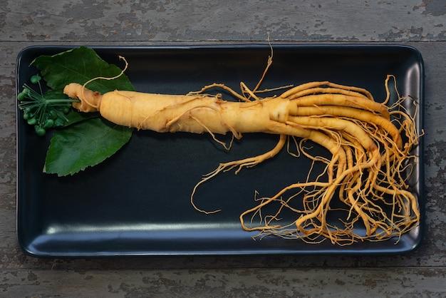 Świeży korzeń żeń-szenia na czarnej płycie z zielonymi liśćmi i jagodami