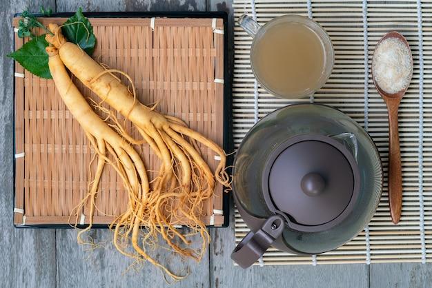 Świeży korzeń żeń-szenia z filiżanką gorącej herbaty, pojęcie zdrowego napoju