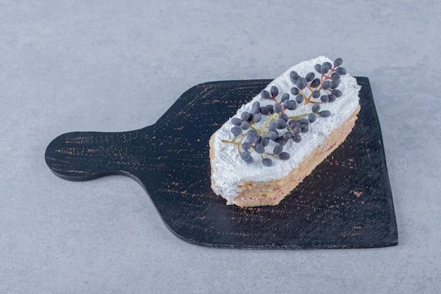 Świeży kremowy kawałek ciasta z jagodami na czarnej drewnianej desce do krojenia