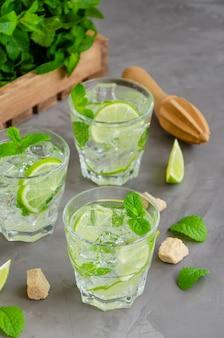 Świeży letni napój mojito z plastrami limonki, miętą, kostkami lodu i brązowym cukrem w szklance