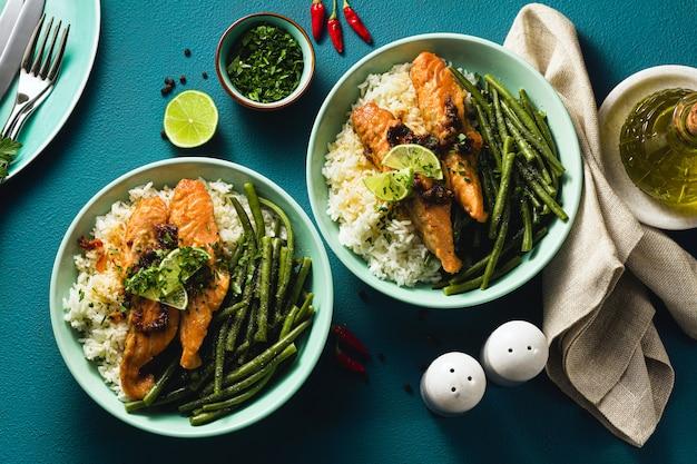 Świeży łosoś smażony z imbirem i czosnkiem w mleku kokosowym, z ryżem basmati i zieloną fasolą w talerzach na stole. zdrowy przepis dla całej rodziny.