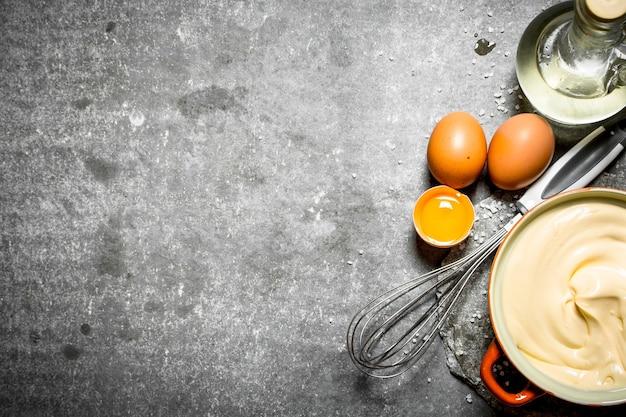 Świeży majonez ze składnikami i trzepaczką. na kamiennym stole.