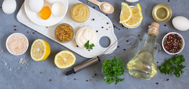 Świeży majonez ze składnikami i trzepaczka nad kamiennym stołem