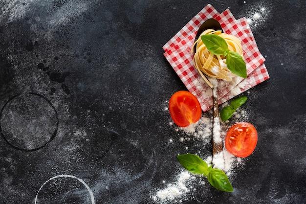 Świeży makaron tagliatelle domowej roboty na drewnianej łyżce ze składnikami makaronu pomidory, surowe jajko, liść bazylii na ciemnym betonowym stole. koncepcja gotowania. widok z góry z miejscem na kopię.