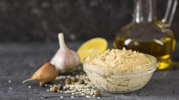 Świeży makaron tahini z nasion sezamu z oliwą z oliwek i sokiem z cytryny na czarnym drewnianym stole