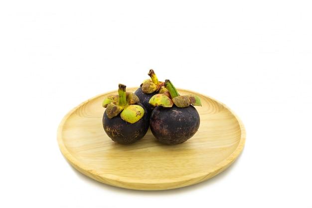 Świeży mangostan na drewnianym talerzu odizolowywającym na białym tle