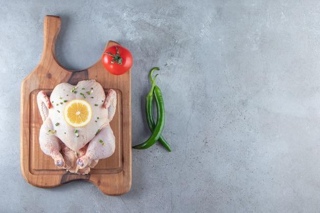 Świeży marynowany cały kurczak na desce do krojenia obok warzyw, na marmurowym tle.