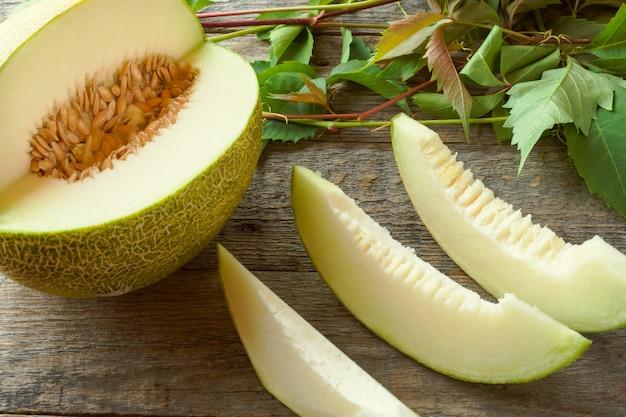 Świeży melon pokrajać na kawałki na drewnianym stole