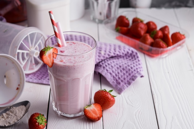 Świeży milkshake z truskawkami na lekkim stole.