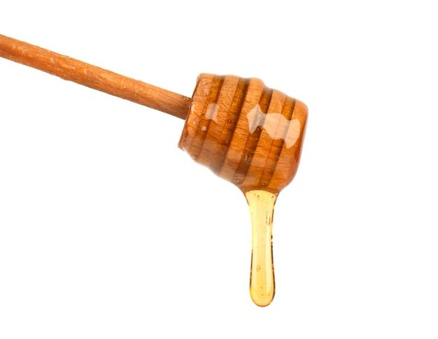 Świeży miód kapie z miodowej chochli odizolowywającej na bielu, pszczoła produkty organicznie naturalnymi składników pojęciem