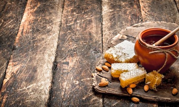 Świeży miód z migdałami. na drewnianym tle.
