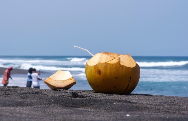 Świeży młody owoc kokosa na ciemnej, piaszczystej plaży w pantai dewa ruci purworejo, indonezja, wybrany fokus z zamazanymi i nierozpoznanymi ludźmi robiącymi zdjęcie w tle