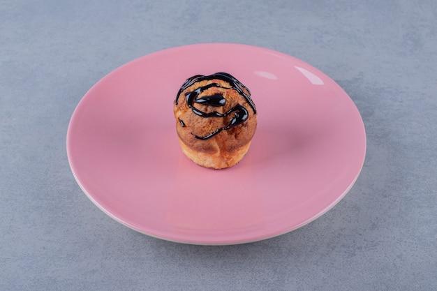 Świeży muffin domowej roboty z kawałkiem czekolady na różowym talerzu na szarej powierzchni