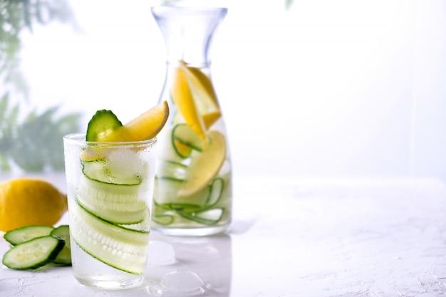 Świeży napój z ogórkiem, cytryną i ziołami rozmarynu. zimna letnia lemoniada. na białej ścianie