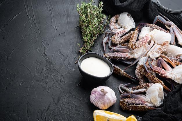 Świeży niebieski krab pływacki krab koń, krab niebieski, zestaw pazurów kraba kwiat, na czarnym tle, z copyspace i miejsca na tekst