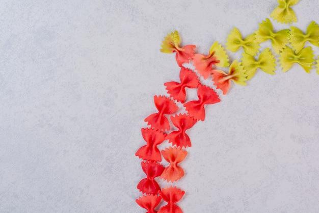 Świeży niegotowany kolorowy makaron na białej powierzchni