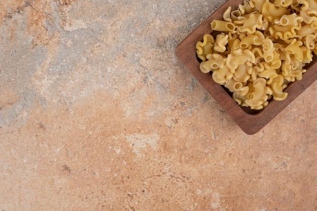 Świeży niegotowany makaron na drewnianej misce na tle marmuru