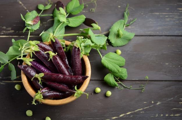 Świeży organicznie purpurowy zielony groszek w drewnianym pucharze na nieociosanym drewnianym stole.