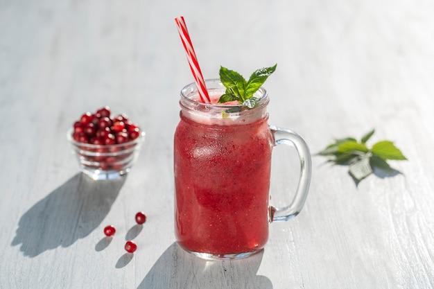 Świeży organiczny czerwony koktajl w szklanym kubku na białym stole, z bliska. orzeźwiający letni napój owocowy. pojęcie zdrowego odżywiania. koktajl żurawinowo-malinowy w słoneczny dzień