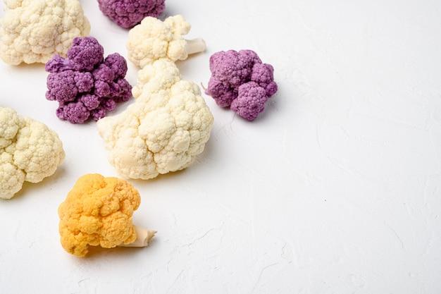Świeży organiczny kalafior pokrojony na małe kawałki, na białym tle kamiennego stołu, z miejscem na kopię tekstu