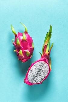 Świeży organiczny owoc smoka (pitaya lub pitahaya) przecięty na pół na niebieskim tle mięty z cieniami. kreatywny płaski układ z modnymi egzotycznymi owocami w żywych odważnych różowych i zielonych kolorach.