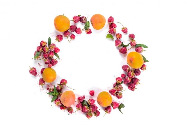 Świeży organiczny wieniec malin i moreli. koncepcja zbiorów lato i jagody. wegańskie, wegetariańskie, surowe jedzenie.