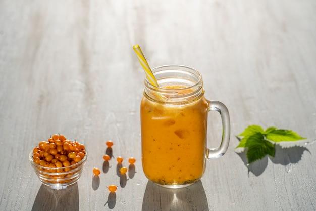 Świeży organiczny żółty koktajl w szklanym kubku na białym drewnianym stole, z bliska. orzeźwiający letni napój owocowy. pojęcie zdrowego odżywiania. rokitnik z koktajlem miodowo-wodnym w słoneczny dzień