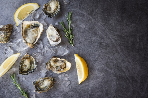 Świeży ostryga owoce morza na czarnym talerzu. otwarta skorupa ostryg z przyprawami ziołowymi rozmarynem cytrynowym serwowana na stole i lodzie zdrowe owoce morza surowa ostrygowa kolacja w restauracji dla smakoszy