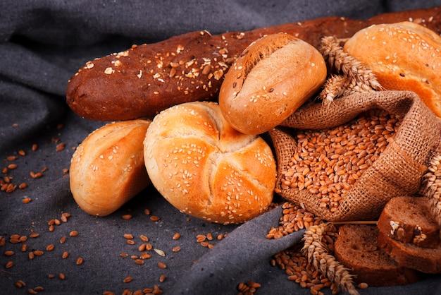Świeży pachnący chleb na stole. koncepcja żywności. piekarnia, chrupiące bochenki chleba i bułki. asortyment pieczonego chleba