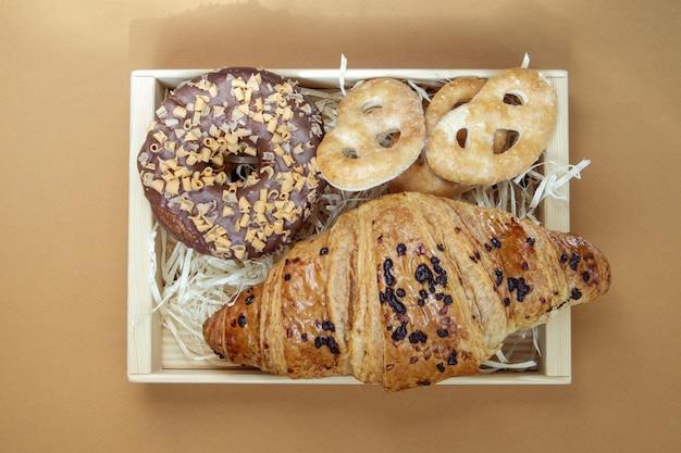 Świeży pączek czekoladowy, croissant i ciasteczka na delikatnym kawowym lub brązowym tle. pyszne desery. koncepcja słodkiej żywności do projektowania i drukowania. widok z góry, układ płaski. skopiuj miejsce.