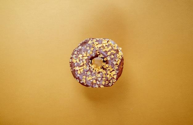 Świeży pączek czekoladowy na białym tle na tle kawy. pyszny deser z błyszczącą polewą czekoladową. koncepcja słodkiego jedzenia z jednym okrągłym czekoladowym pączkiem do zaprojektowania i nadruku. widok z góry, układ płaski.