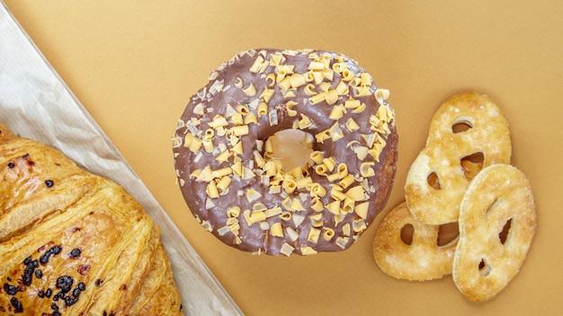 Świeży pączek czekoladowy, rogalik i biszkopt na delikatnym kawowym lub brązowym tle. pyszne desery. koncepcja słodkiej żywności do projektowania i drukowania. widok z góry, układ płaski. skopiuj miejsce.