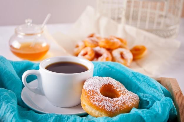 Świeży pączek z filiżanką kawy na stole