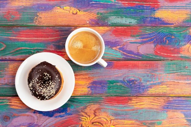 Świeży pączek z kawą na drewnianej powierzchni