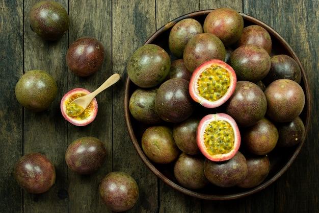 Świeży pasyjny owocowy plasterek w drewnianym pucharze na stole