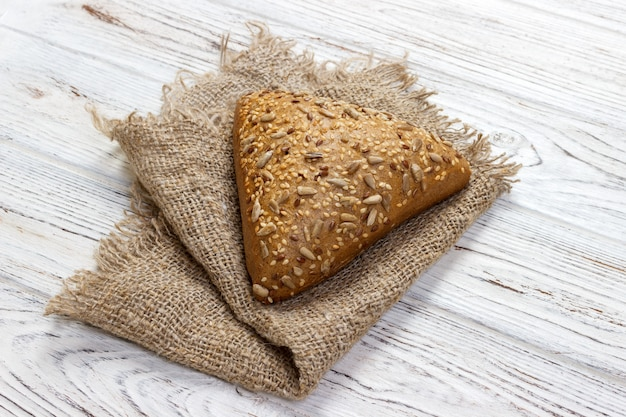 Świeży pieczony chleb lub babeczka z sezamem i słonecznikiem na drewnianym stole